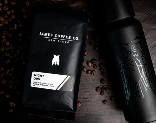 Top view of coffee beans with packaged coffee and refillable hot drink bottle