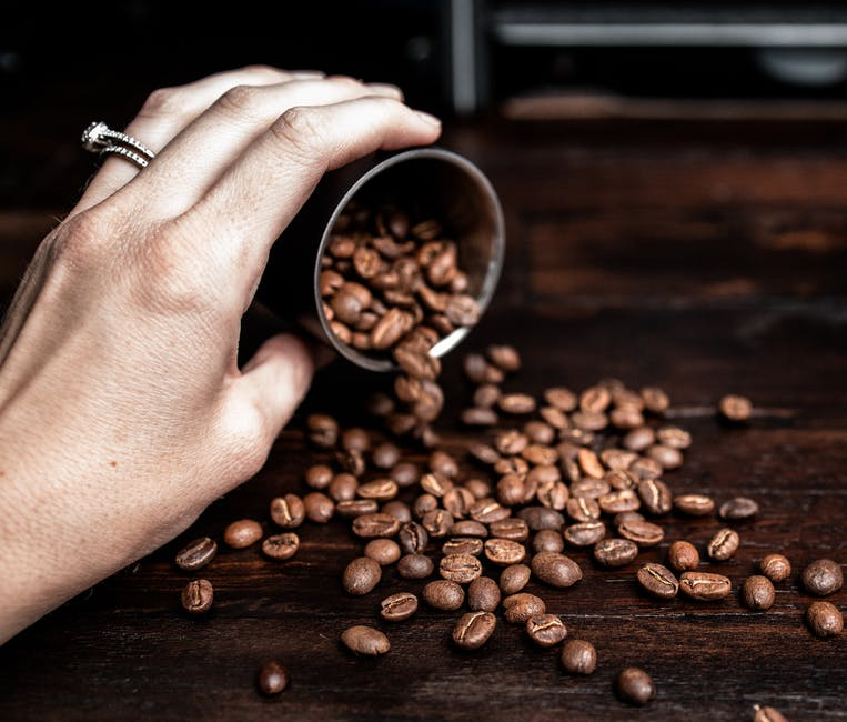 Woman pouring coffee beans on table