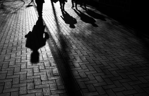 Silhouettes of people walking on sidewalk in evening