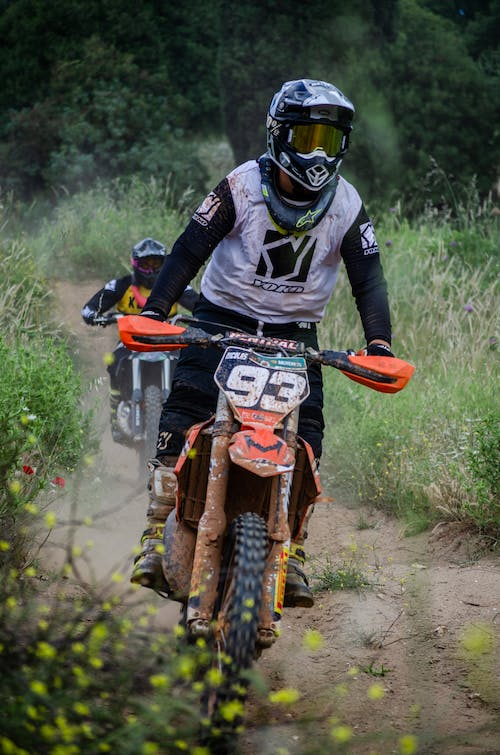 Unrecognizable racers in helmets competing in enduro while riding motorcycles on dirt path