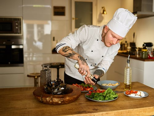 Man in White Chef Hat Slicing Meat on Brown Wooden Chopping Board