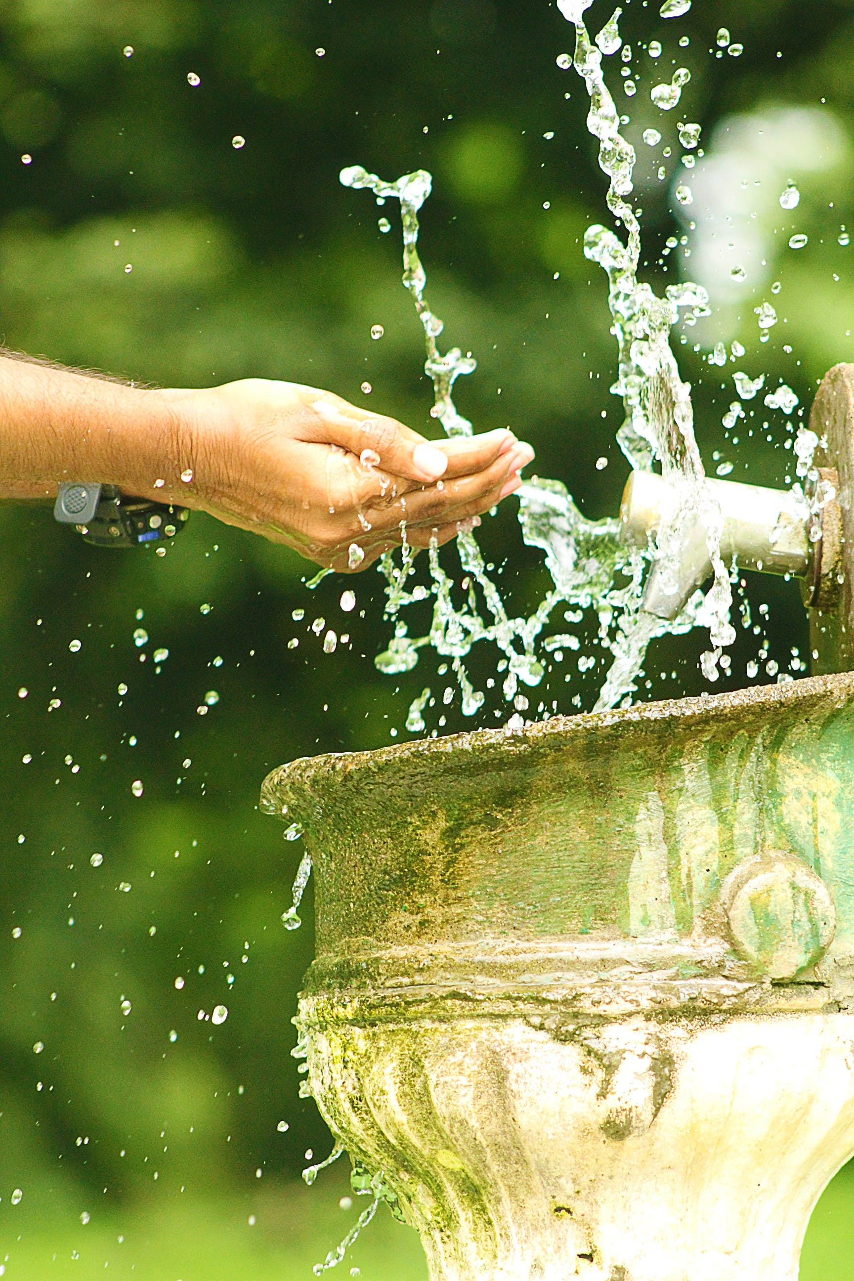 Selective Focus Photography of Person Washing Hand on Water Fountain