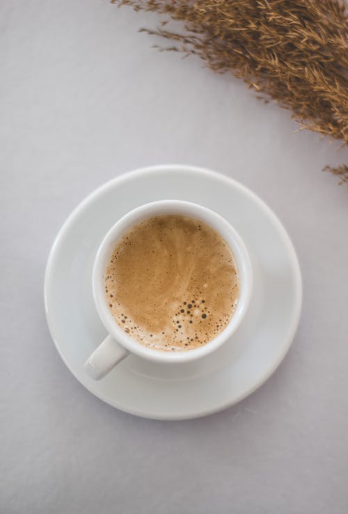 Cup of foamy coffee on white table