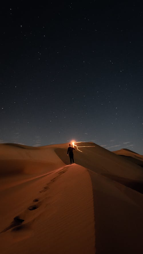 Person Standing on Sand during Night Time