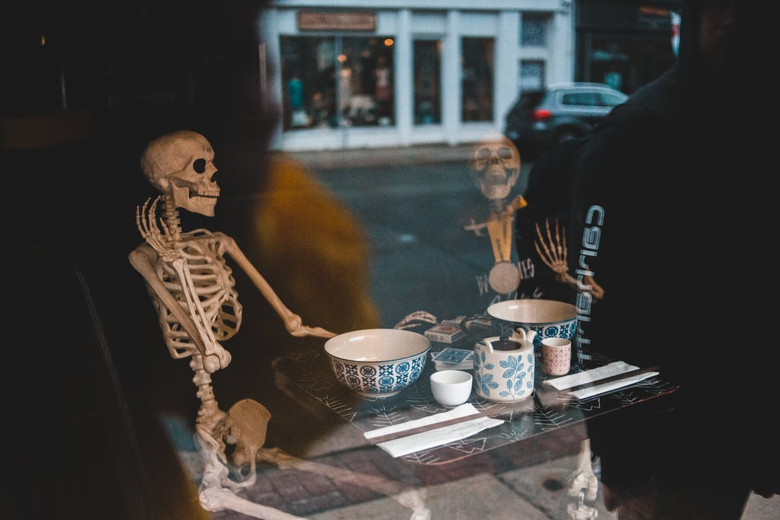 Skeletons at table with dishware in cafe