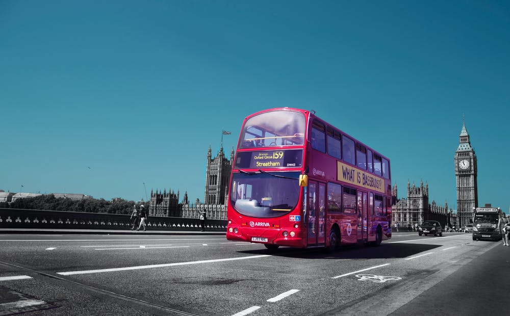 Red double deck bus on the road. | Photo: Pexels