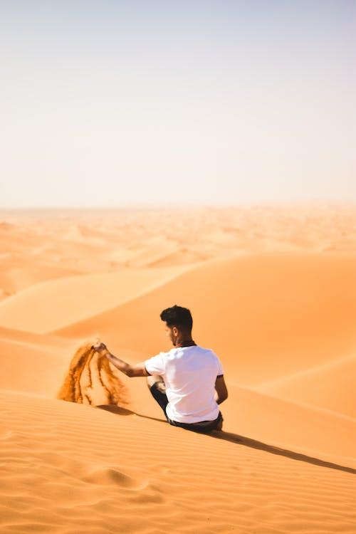 Man in White Shirt Standing on Desert