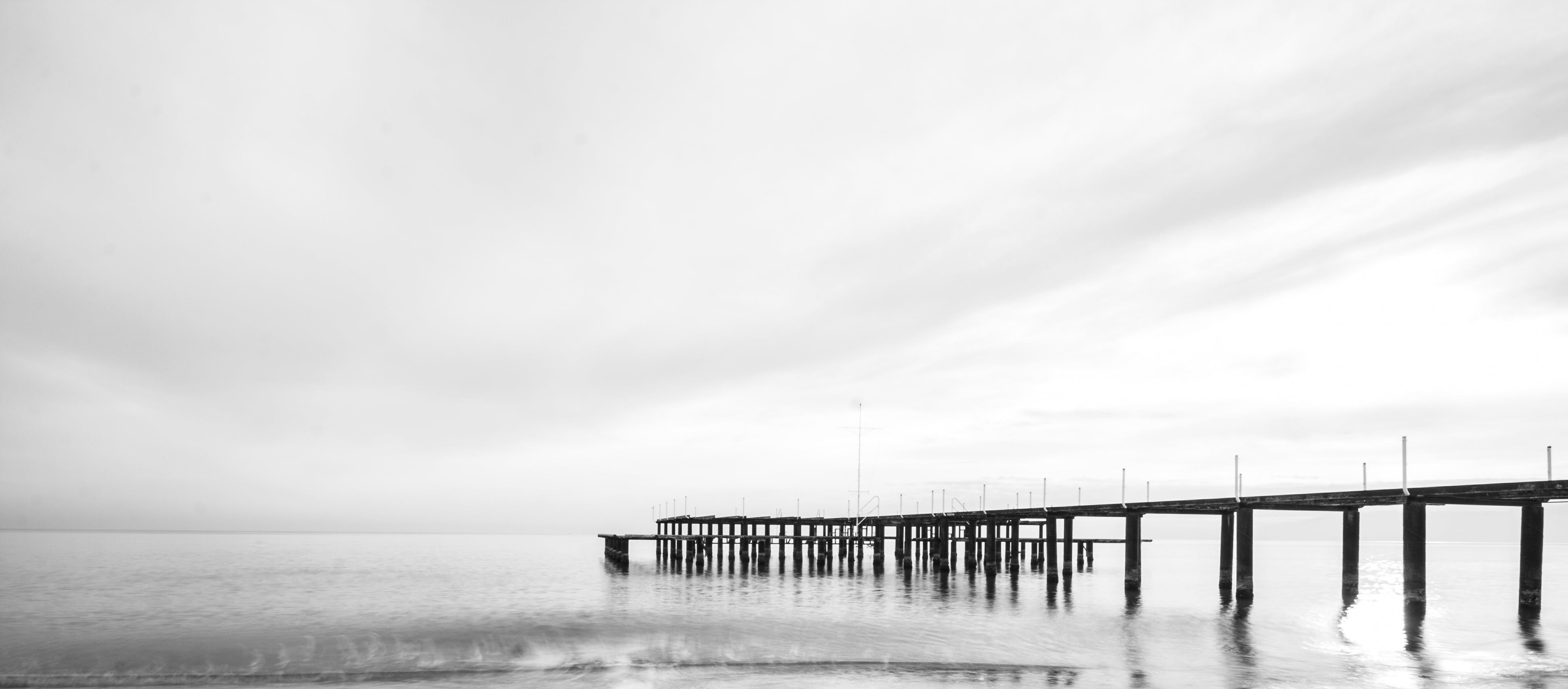 Black Wooden Bridge Under White Sky