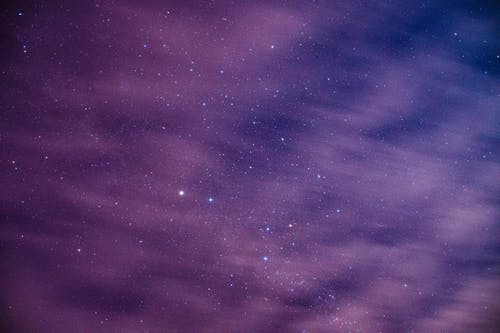 Long exposure of cosmic background with dark night sky with glowing bright stars behind light floating clouds