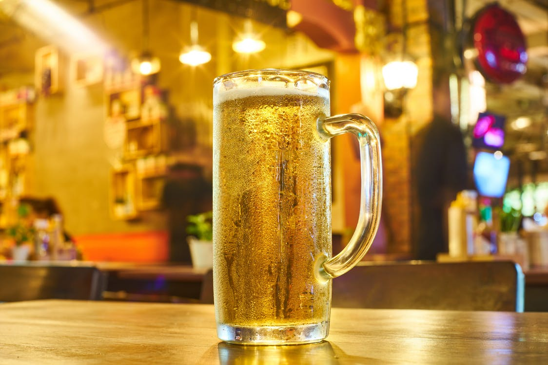 Full Clear Glass Beer Mug on Brown Wooden Counter