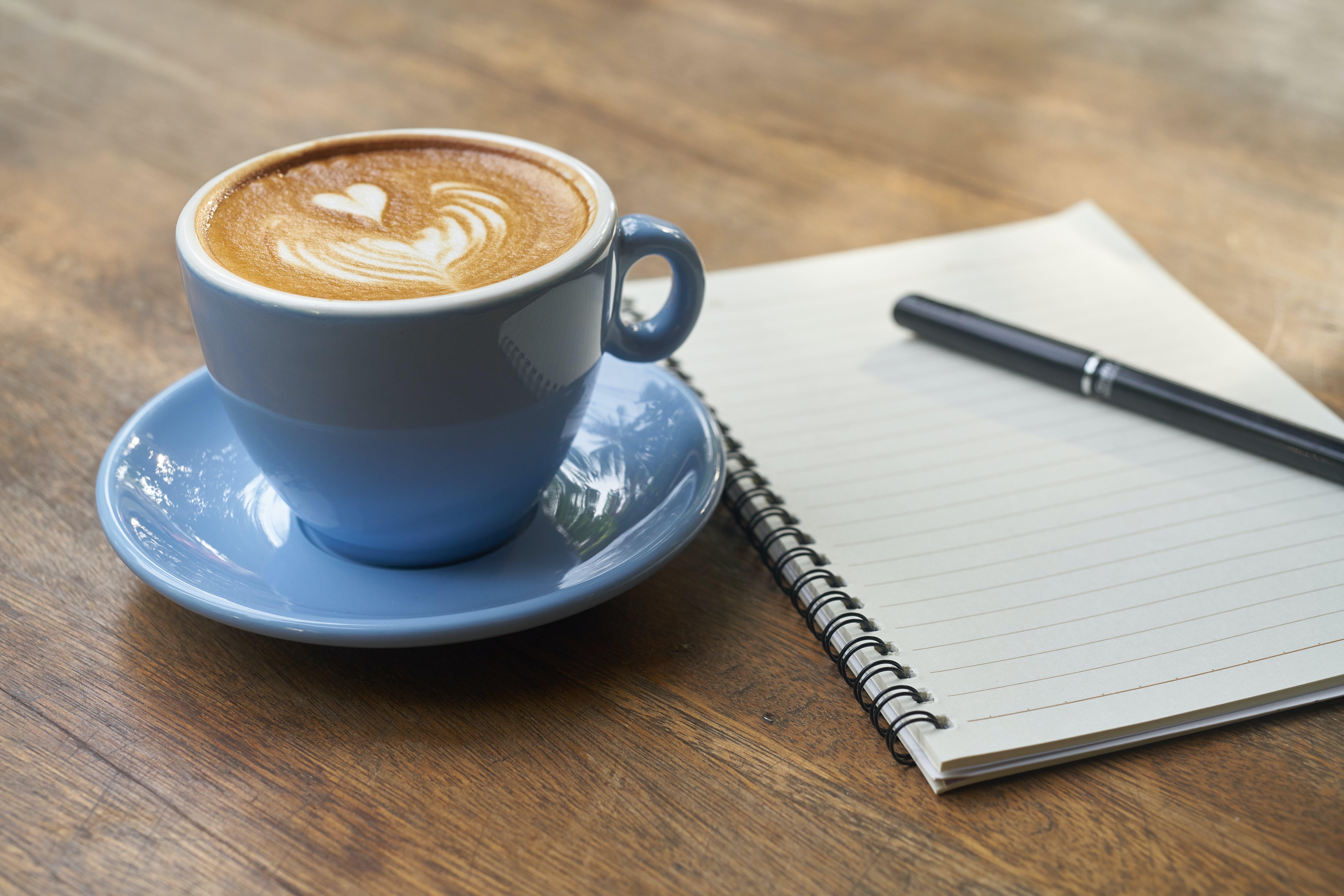 Foto d'estoc gratuïta de art latte, bloc de notes, boli, cafè