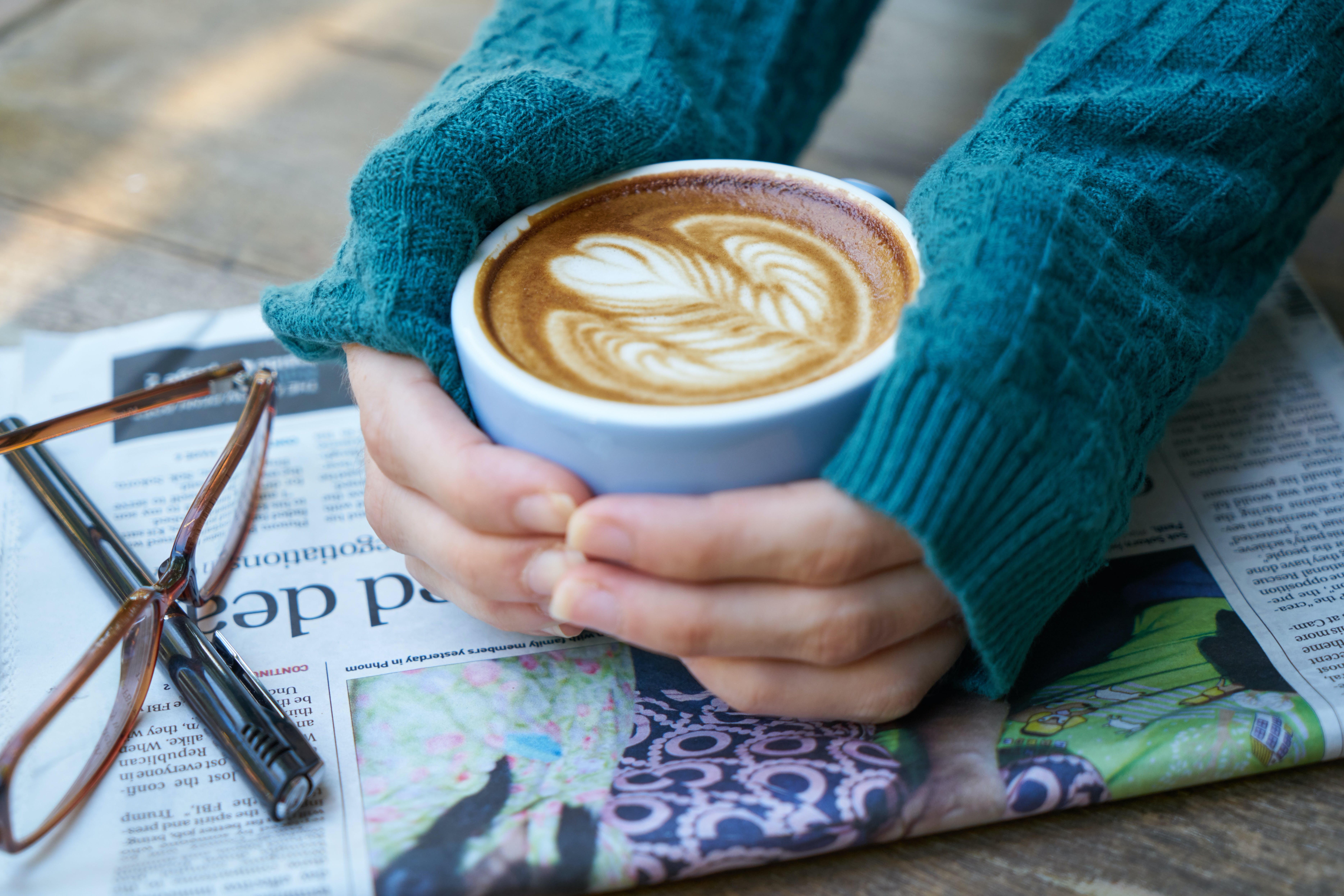 Person Holding Cup of Cappuccino With Both Hands