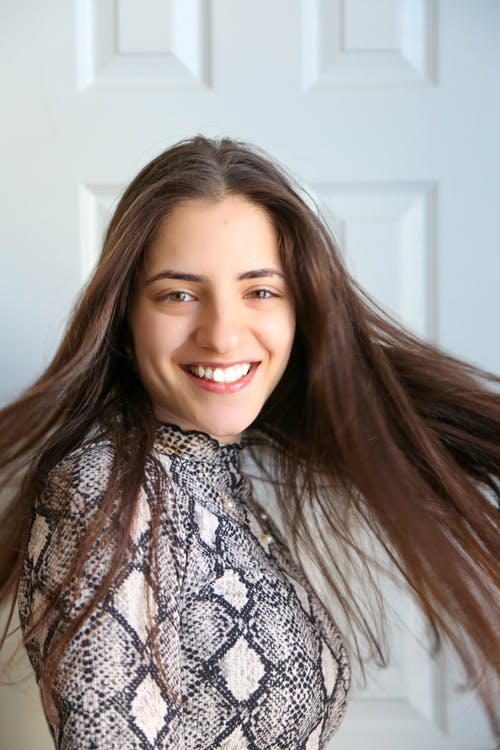 Positive young lady moving hair and smiling