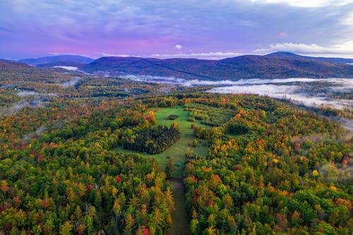Breathtaking landscape of lush autumn forest in highlands against cloudy sundown sky