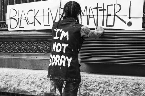Back view of unrecognizable tattooed guy standing on street in front of banner with Black Lives Matter inscription