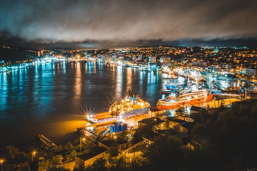Illuminated coastal town at cloudy night