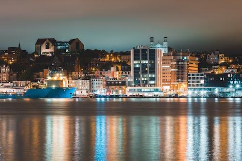 Various ships moored in harbor of coastal illuminated city at night