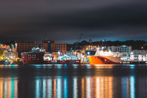 Ships moored in port of modern city at night
