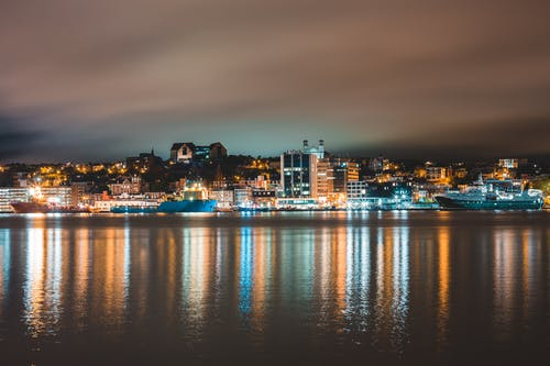 Colorful lights of illuminated coastal city reflecting in water of sea against cloudy night sky in St John s