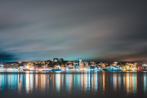 Cloudy night sky over illuminated coastal city and harbor