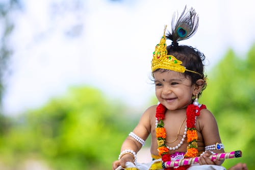 Cheerful Indian baby in traditional costume of Krishna during Janmashtami festival celebration on sunny day