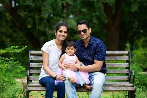 Happy young Indian man and woman embracing adorable little daughter while resting on bench in green park