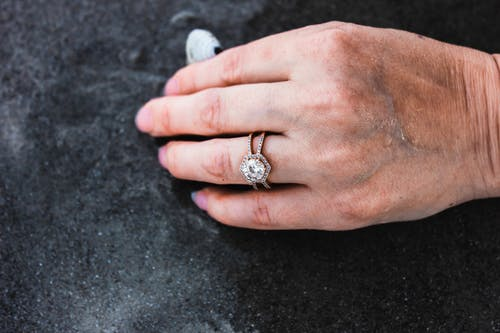 From above of crop faceless female with brilliant ring on finger touching black sand during  summer holidays