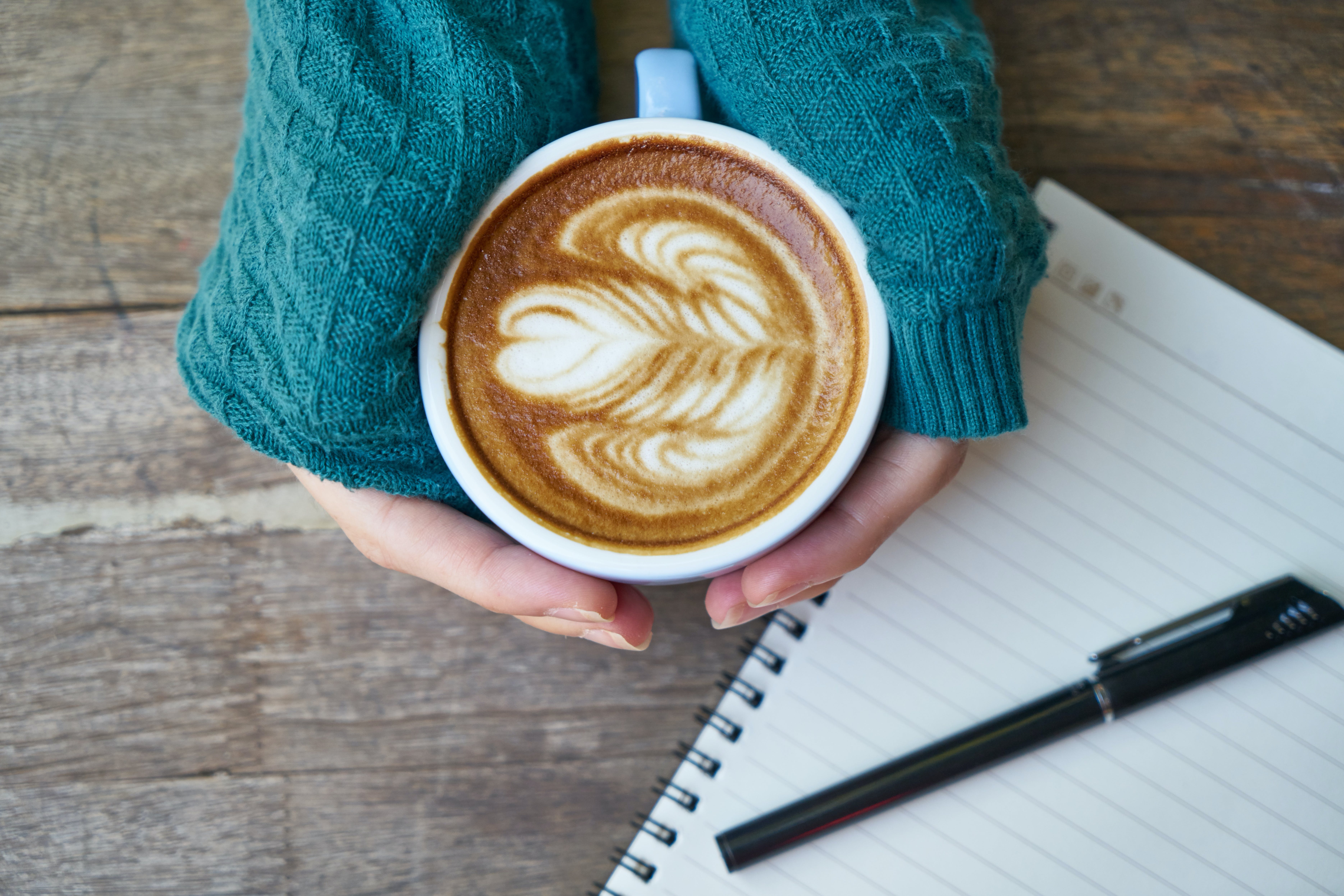 Person Holding Cup of Coffee Latte Near Notebook and Pen