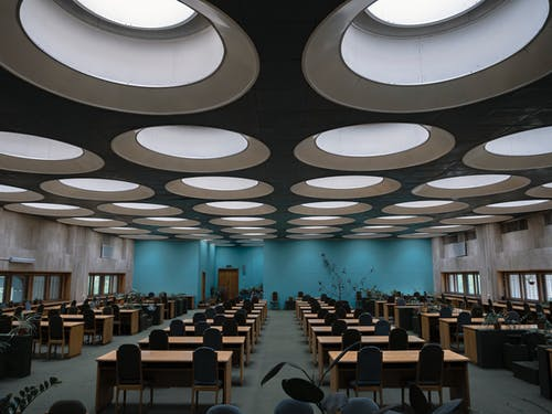 Wooden tables and chairs placed in rows in empty room of Vernadsky National Library of Ukraine with unusual round windows on ceiling