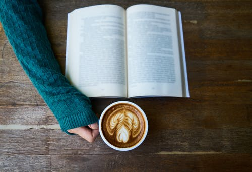 Person Having Cup of Latte While Reading Book
