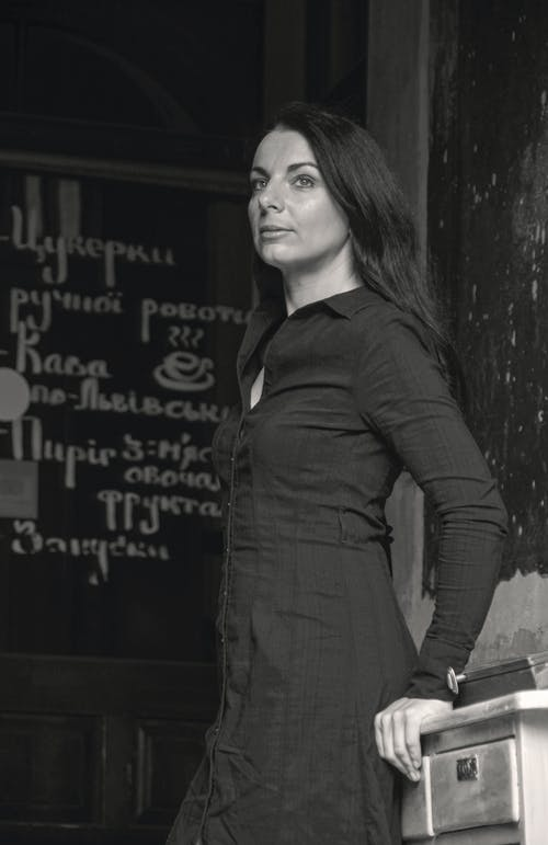 Side view of black and white pensive female in casual clothes leaning on wooden table and looking away