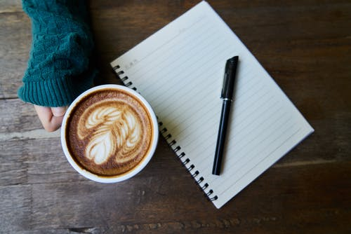 Black Pen on Ruled Paper Beside Cup of Latte