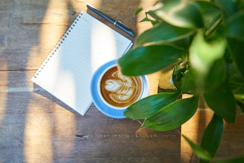 Cup of Latte Beside Spiral Notebook With Black Pen