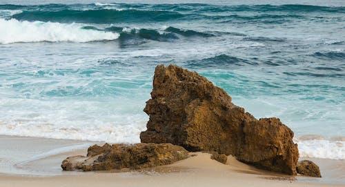 Sandy seashore with rough rock washing by foamy waves