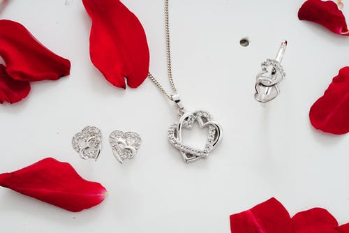 Set of shiny silver accessories among red petals