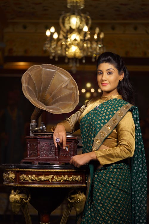 Ethnic woman in traditional dress standing near vintage gramophone