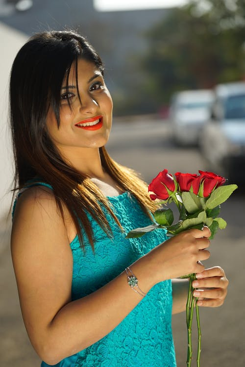 Smiling ethnic woman with bouquet of flowers