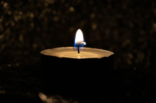 Bright burning flame of candle placed on surface against blurred dark greenery of street