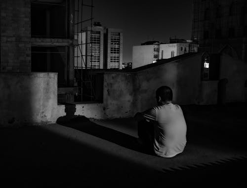 Lonely man sitting on rooftop at night