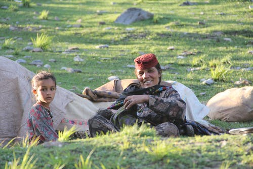 Ethnic woman with kid resting on green meadow