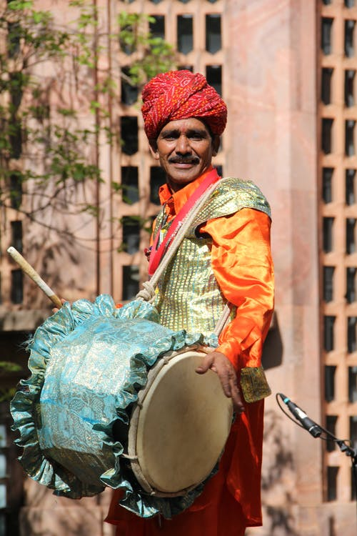 Aged Indian male in colorful authentic outfit playing musical instrument while standing on stage during festival