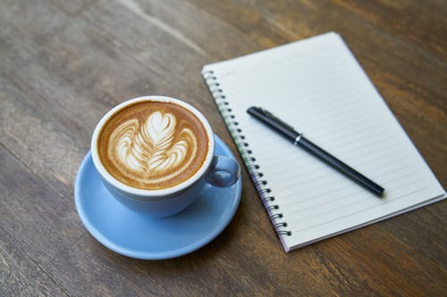 Cup of Latte Beside Spiral Notebook
