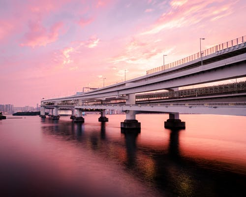Long concrete bridge crossing calm river under cloudy sunset sky reflecting in water surface
