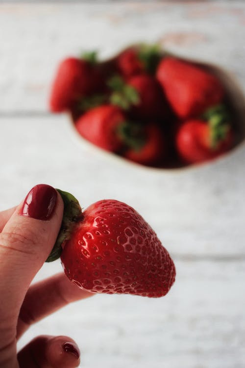 Person Holding Red Strawberries on White Table