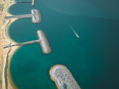 Sandy beach and stone barrier with fast boat