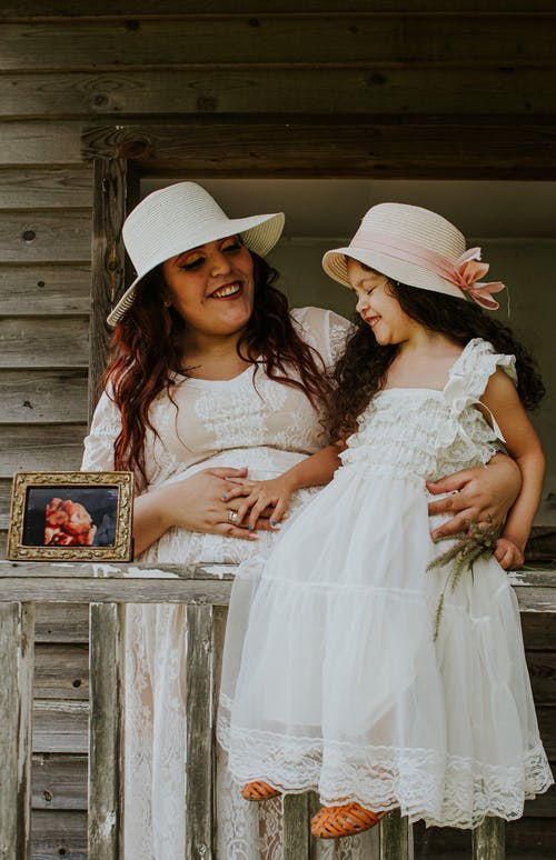 Cheerful woman in straw hat embracing content daughter in white dress touching belly on fence of terrace near photo of fetus