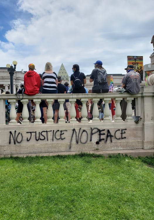 Back view of anonymous people resting on aged ornamental fence with written title NO JUSTICE NO PEACE above grass lawn in town