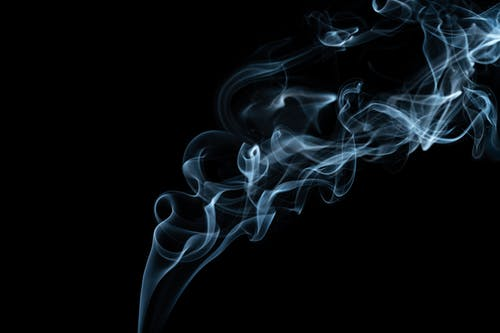 Wavy smoke stream on black background in evening