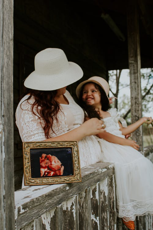 Unrecognizable expectant mother near positive child on porch with photo