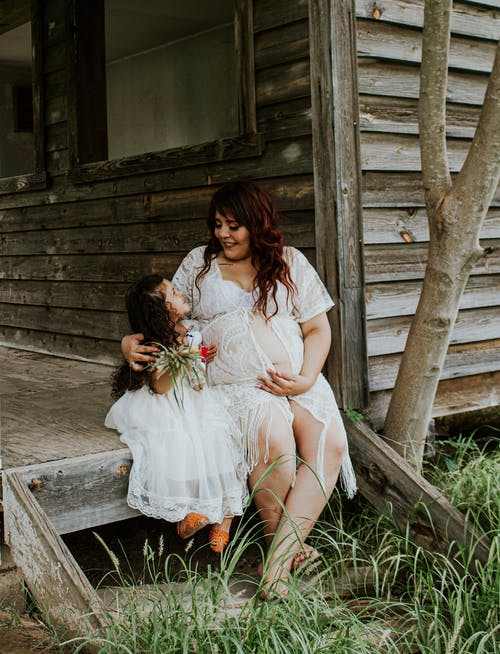 Smiling pregnant woman embracing daughter on old terrace